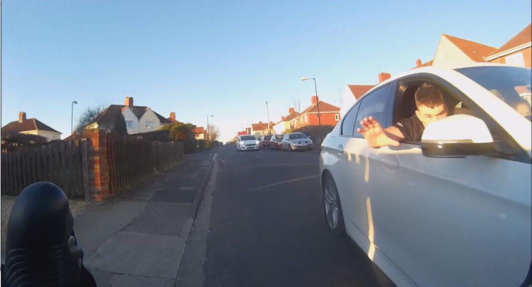 un conductor empuja a un ciclista fuera de la carretera