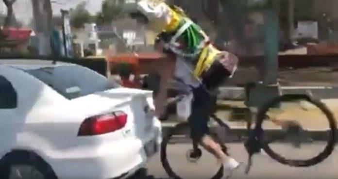 accidente de un ciclista con un santo a sus espaldas