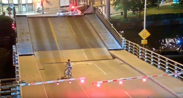 ciclista se salta un semáforo en rojo en puente levadizo