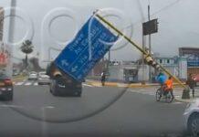ciclistas a punto de ser aplastados por un cartel